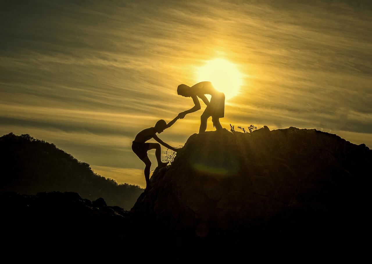 Chłopak pomagający drugiemu wspiąć się na górę