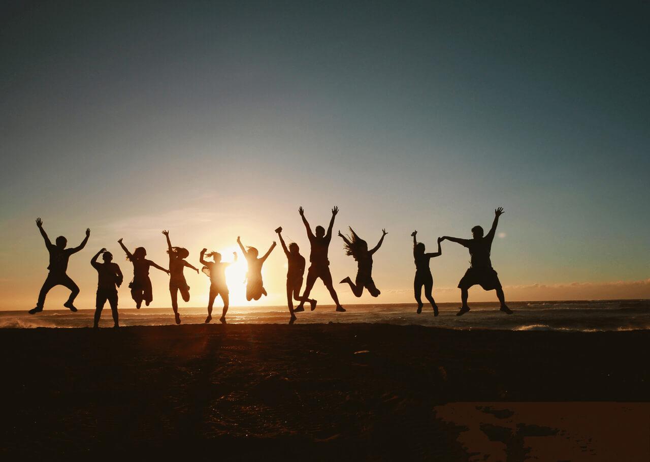 Skaczący przy zachodzie słońca ludzie