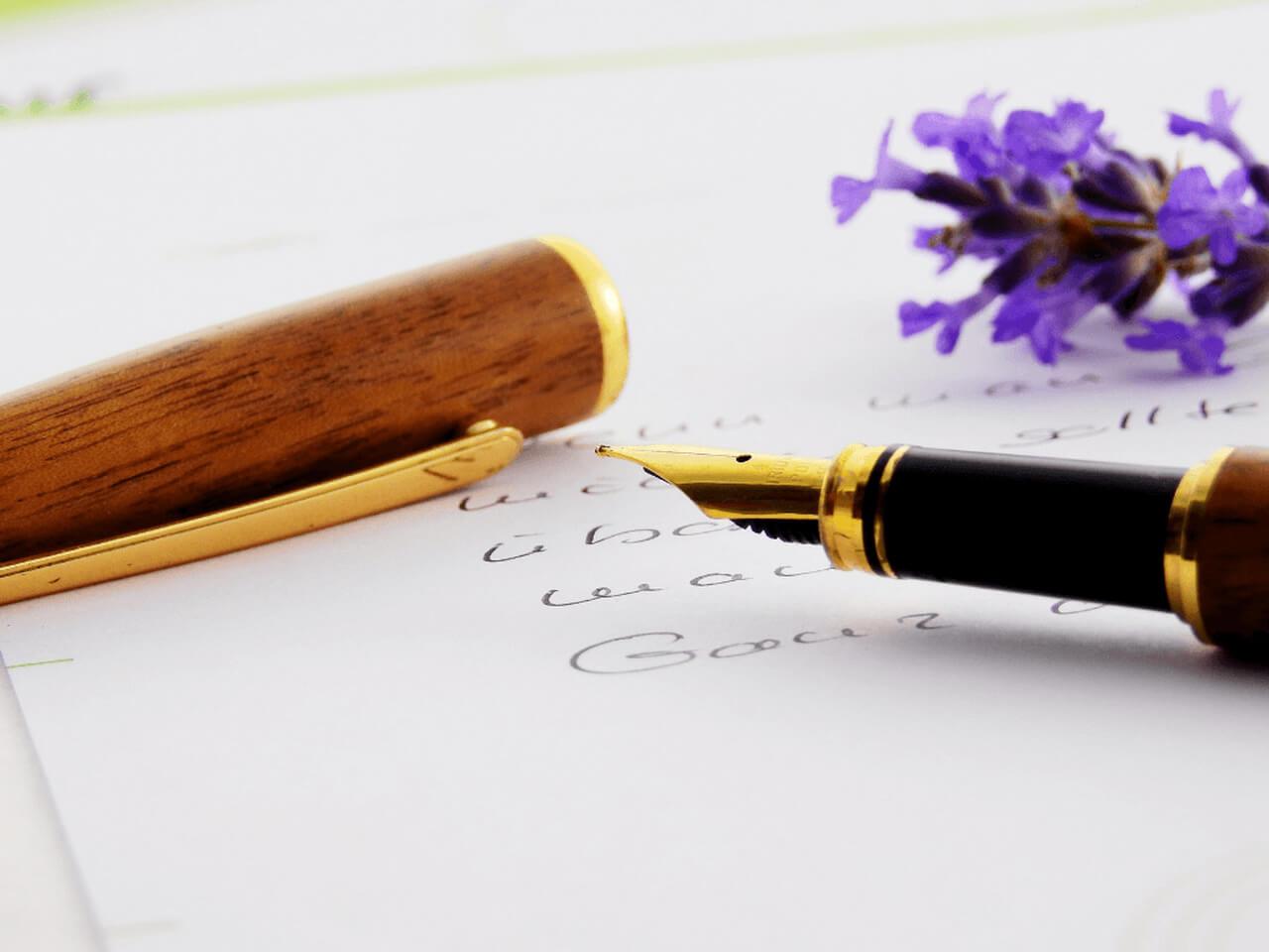 Kartka papieru a na niej pióro i kwiatek